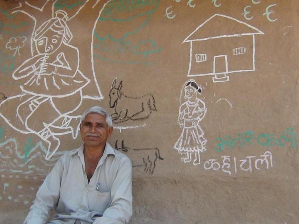 Kalubhai Wala with a village painting behind him.