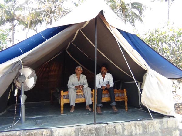 Kalubhai & his associate Jagabhai sitting inside tent.
